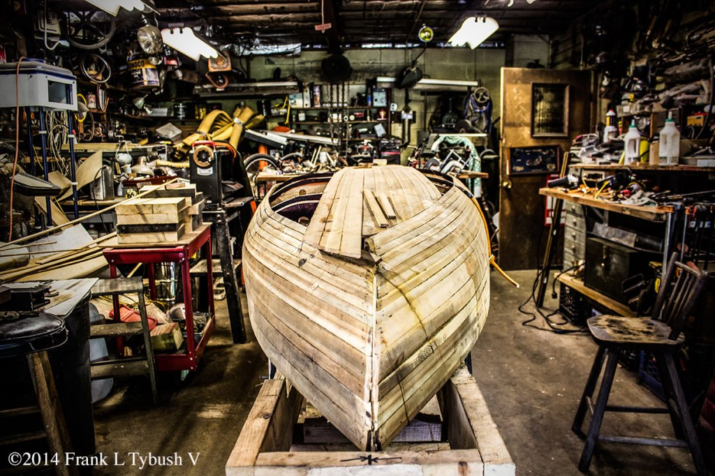 A cluttered workshop with a half-made canoe in the center of it.