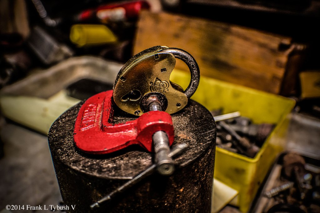 A red clamp that is holding together a brass lock in the shape of a heart/