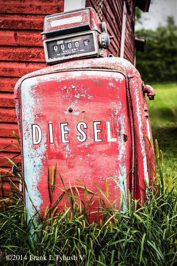 """An old, faded gas pump in front of a barn. Overgrown grass surrounds it. The word """"Diesel"""" is painted on the side."""