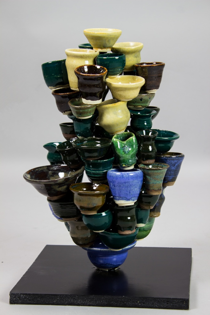 A sculpture that is dozens of small ceramic cups glued together into an abstract shape.